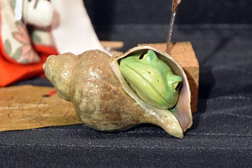 巻貝の隙間からカエルが顔を出している